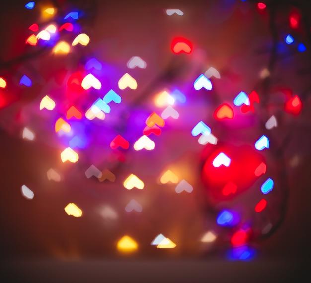 Een wazige achtergrond met bokeh in de vorm van harten in verschillende kleuren