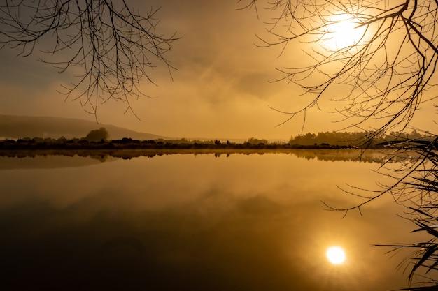 Een wazige start van de dag boven het meer bij zonsopgang