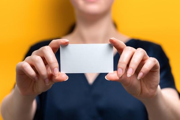 Een wazige vrouw houdt een lege witte kaart vast. detailopname. gele achtergrond. bespotten.