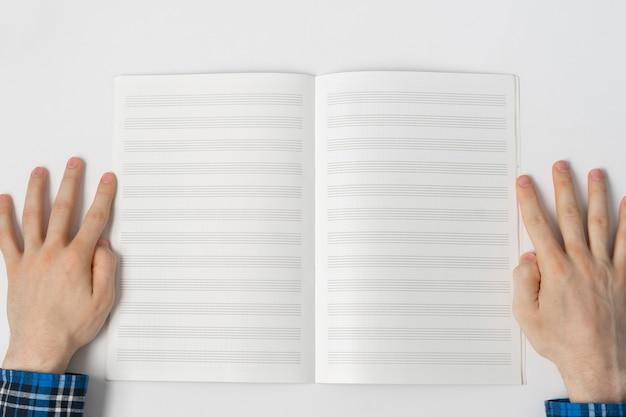 Een weergave van bovenaf, persoon die de notities in notitieboekje, lege blanco papier met kopie ruimte opneemt