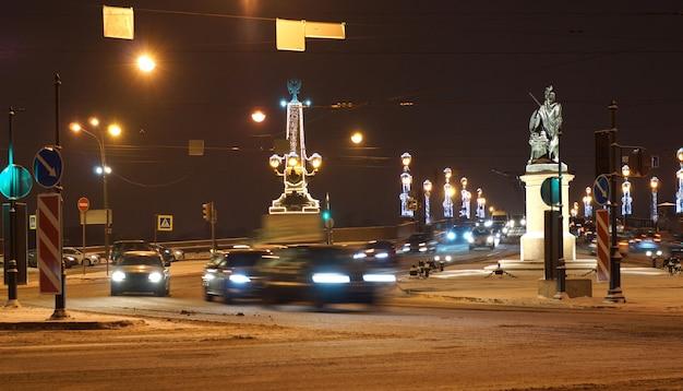 Een weg met felle lantaarns en brandende slingers in sint-petersburg. auto's rijden met koplampen aan
