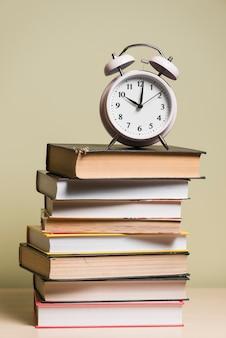 Een wekker bovenop gestapelde boeken over houten bureau