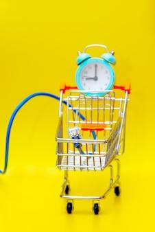 Een wekker en een mini-kar met een kopieermachine op een gele achtergrond. computerkabel naar het winkelwagentje, online winkelconcept. selectieve focus