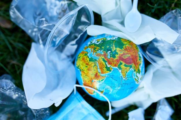 Een wereldbol in een stapel van verspreide afval op een groen gras