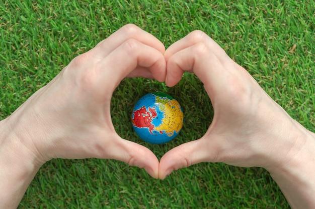 Een wereldbol op het weelderige groene gras, handen in de vorm van een hart. dag van de aarde. planeet aarde