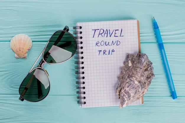 Een wereldreis plannen. notebook, schelpen, pilotenbril op een blauwe houten achtergrond.