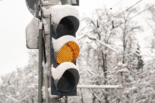 Een werkend verkeerslicht op een straat in de stad in de winter. het gele lampje brandt, maak je klaar om te vertrekken. oost-europa