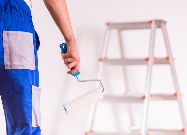 Een werkende man houdt een gereedschap in zijn hand en is klaar om te werken.