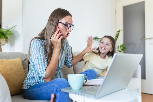 Een werkende moeder die aan het multitasken is. alleenstaande moeder met een kind dat probeert te werken. bezorgde vrouw die thuis werkt terwijl haar dochter haar niet toelaat. quarantaine-isolatie tijdens de covid-19 gezondheidscrisis