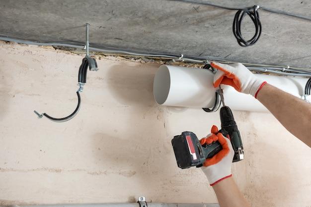 Een werknemer bevestigt ventilatiepijpen aan het plafond met een schroevendraaier