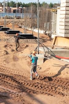 Een werknemer brengt elementen over voor de installatie van de bekisting op de bouwplaats. monolithische betonnen bekisting tijdens de bouw van een woongebouw.