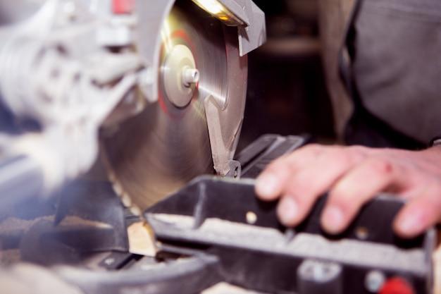 Een werknemer concentreert zich op het verwerken van een houten bord op een cirkelvormige machine