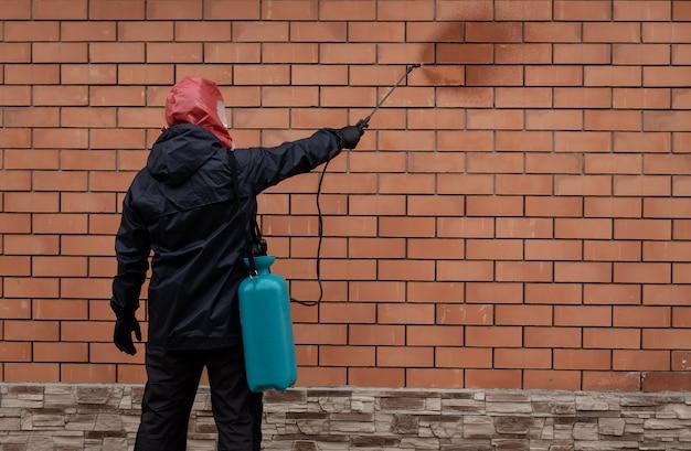 Een werknemer in een gasmasker en uniform sproeien van ontsmettingsmiddelen op een bakstenen muur van een gebouw met een spuitpistool preventie van de verspreiding van coronavirus