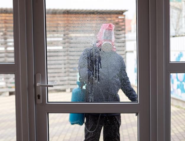 Een werknemer in een gasmasker en uniform, spuit een ontsmettingsmiddel met een spuitpistool op een glazen deur voorkomen van de verspreiding van de coronavirus-epidemie wazige achtergrond, binnenaanzicht