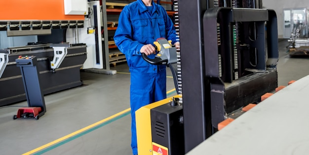 Een werknemer in een magazijn gebruikt een handpalletstapelaar om pallets te vervoeren.