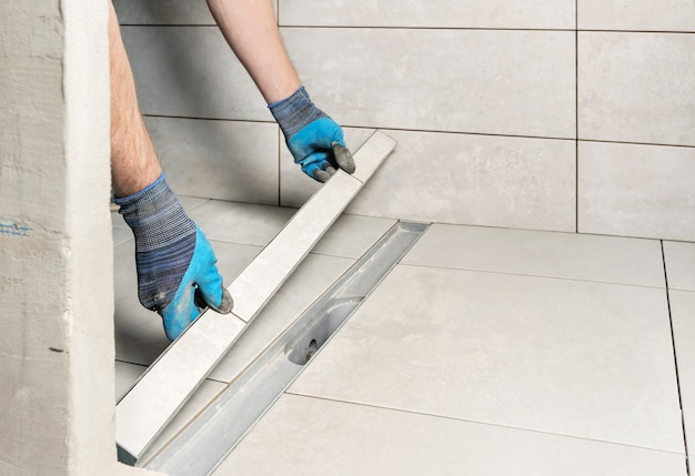 Een werknemer installeert een afvoerdeksel versierd met keramische tegels in de badkamer