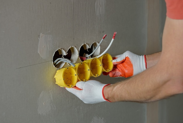 Een werknemer installeert een groep contactdoosdozen in gipsplaat