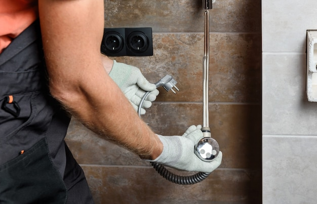 Een werknemer installeert een verwarmingselement in de handdoekverwarmer in de badkamer.