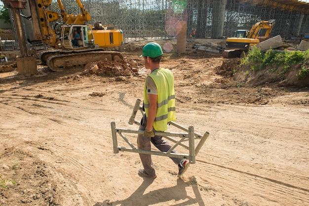 Een werknemer met een veiligheidshelm draagt delen van de steiger over een bouwplaats