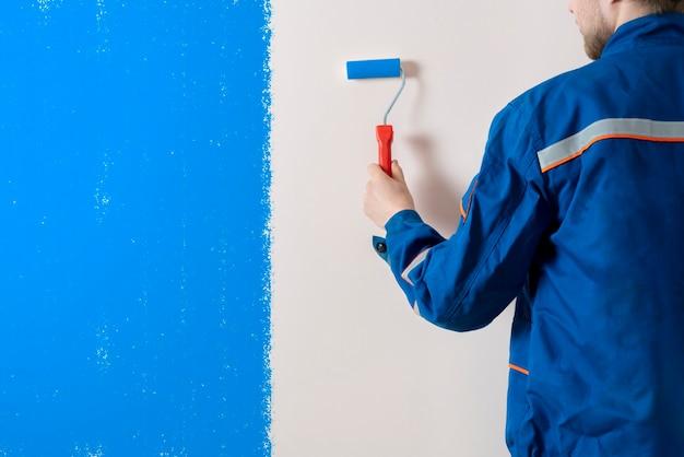 Een werkschilder die het muuroppervlak schildert met een roller, een man aan het werk die een kamer decoreert