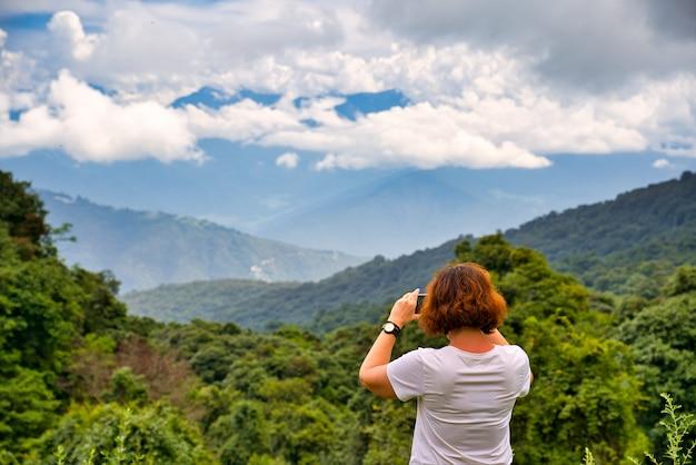 Een westerse reiziger met bruin haar verzamelde foto's van een weelderig berglandschap in de bhutan himalaya met een wit shirt met korte mouwen. blauwe en zonnige hemel met weinig wolken.