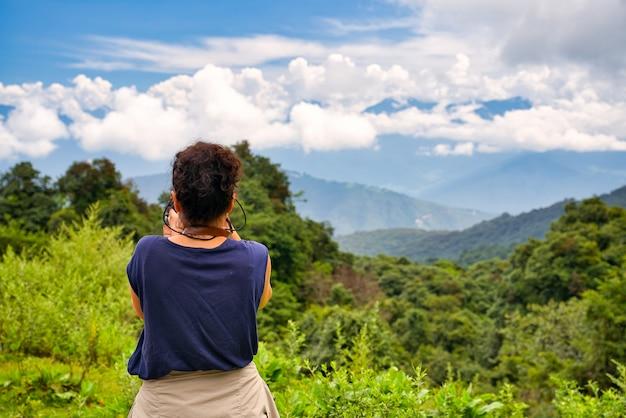 Een westerse reiziger met donker haar verzamelde foto's van een weelderig berglandschap in de bhutan himalaya met een blauw t-shirt en verzamelde mouwen. blauwe en zonnige hemel met weinig wolken.