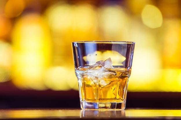 Een whisky met ijs in een glas op de balk (close-up). traditioneel iers drankje