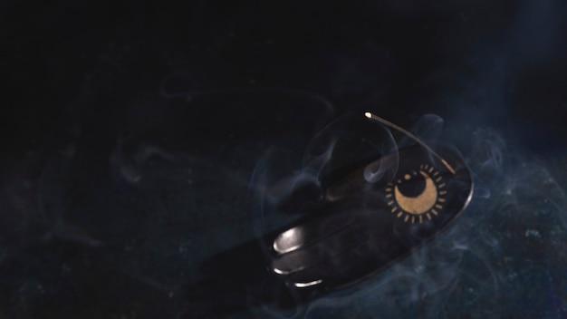 Een wierookstokje op een polssteun rookt op een zwarte achtergrond. kopieer ruimte