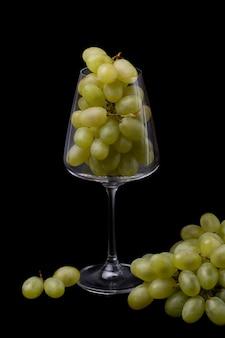 Een wijnglas gevuld met groene druiven op een zwarte achtergrond.