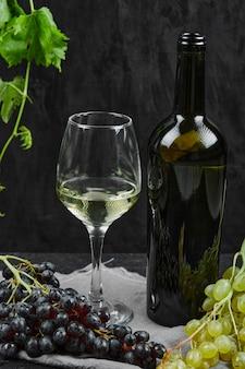 Een wijnglas met een bos rode druiven op tafel.