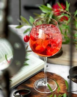 Een wijnglas met kersencocktail gegarneerd met kersen