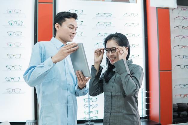 Een winkelbediende die een tablet vasthoudt terwijl een vrouwelijke klant de bril probeert om naar het tabletscherm te kijken terwijl hij tegen de achtergrond van een vitrinekast met lenzenvloeistof in een opticien staat
