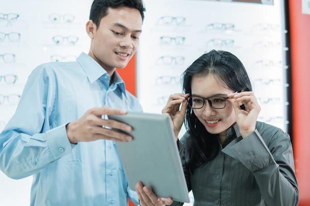 Een winkelbediende die vrouwelijke klanten bedient die op een bril proberen om naar het tabletscherm te kijken terwijl ze tegen de achtergrond van een lenzenvloeistofrek vitrine in een opticien staat