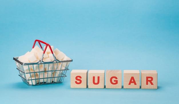 Een winkelmandje vol met blokjes witte suiker. blokletters van diabetes in een kruiswoordraadsel.