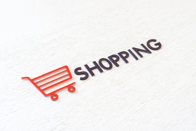 Een winkelwagenpictogramconcept uitgesneden letters, verkoopwinkelzaken, eenvoudig minimalistisch
