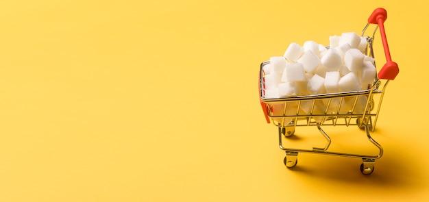 Een winkelwagentje gevuld met suikerklontjes op sinaasappel