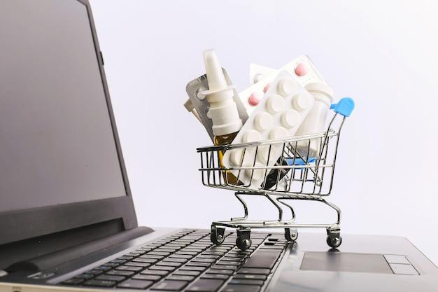 Een winkelwagentje met drugs en pillen staat op de laptop. online verkoopconcept.