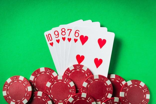 Een winnende pokercombinatie is een straight flush. chips en kaarten op de groene tafel in de pokerclub. geluk of fortuin