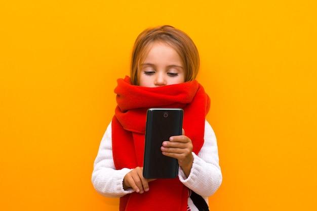 Een winterkind dat naar het scherm van een mobiele telefoon kijkt, kiest geschenken op een geïsoleerde gele achtergrond