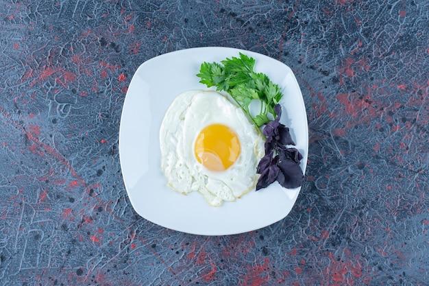 Een wit bord gebakken eieren met kruiden.