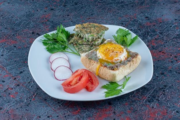 Een wit bord heerlijke toast met vlees en groenten.