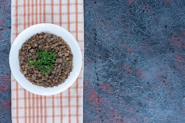 Een wit bord met bonen en kruiden op een tafelkleed