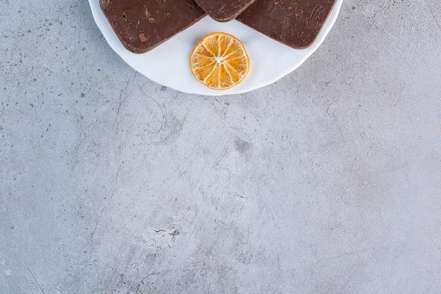 Een wit bord met chocoladekoekjes met gesneden gedroogde citroen op grijs