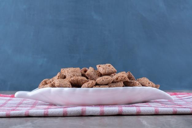 Een wit bord met knapperige heerlijke ontbijtgranen op tafelkleed
