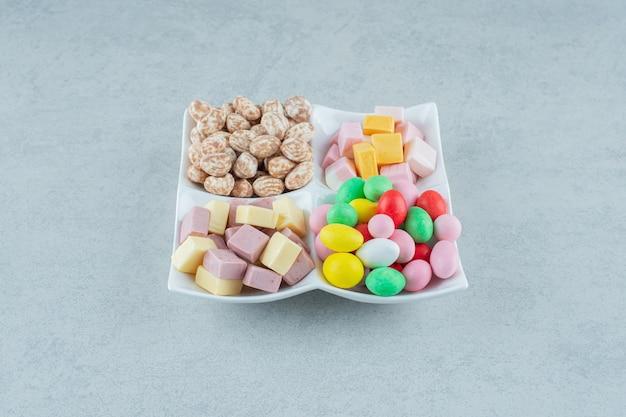 Een wit bord met marshmallows en kleurrijke snoepjes op een witte ondergrond