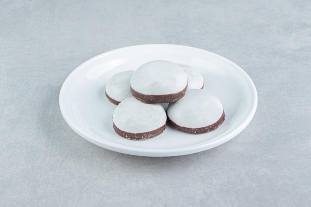 Een wit bord met peperkoekkoekjes met poedersuiker.
