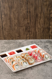 Een wit bord met verschillende soorten heerlijke sushibroodjes op stenen tafel