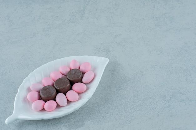 Een wit bord met zoete roze snoepjes en chocoladekoekjes op een witte ondergrond