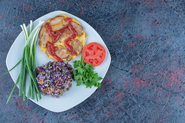 Een wit bord omelet met kruiden en groene uien.