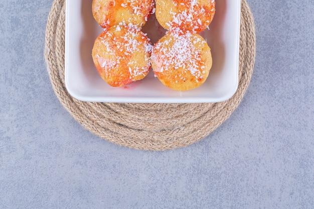 Een wit bord ronde gele koekjes met hagelslag.